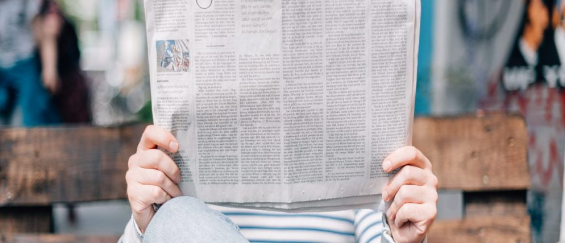 Jemand liest eine Zeitung auf einer Bank